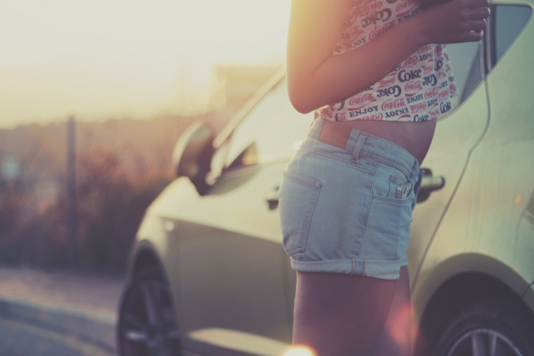 Girl in shorts, waist to thighs, next to yellow Corvette