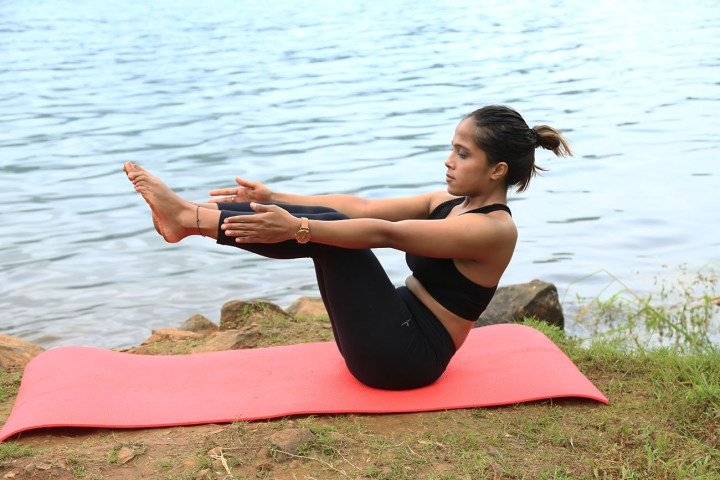 a girl performing the Boat pose in yoga as part of an ab routine