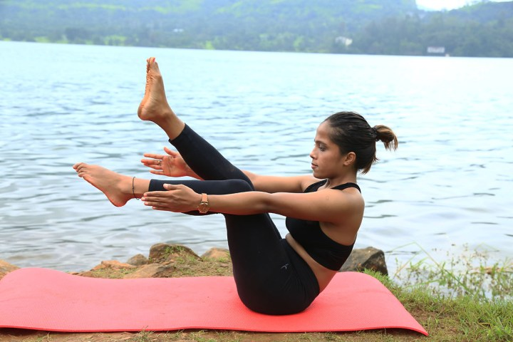 a girl performing an easy variation of the Boat pose in yoga as part of an ab routine