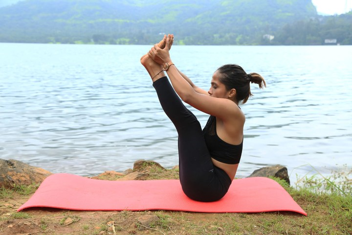 a girl performing a hard variation of the Boat pose in yoga as part of an ab routine