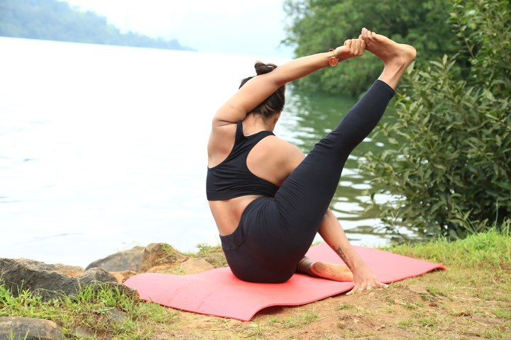 a girl performing the compass Pose to prepare for Shiva pose