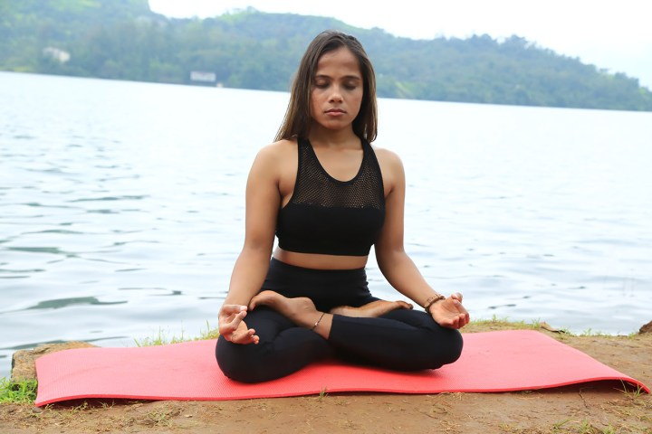 girl performing the lotus pose in yoga beside a lake.