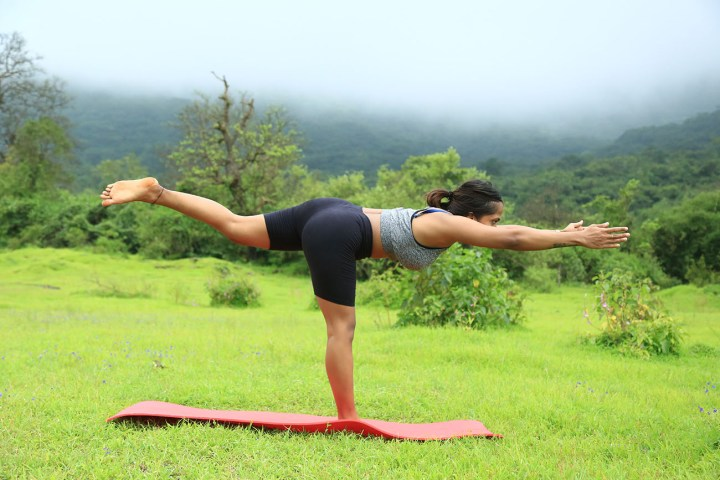 a girl performing the Warrior 3 pose in yoga as part of an ab routine