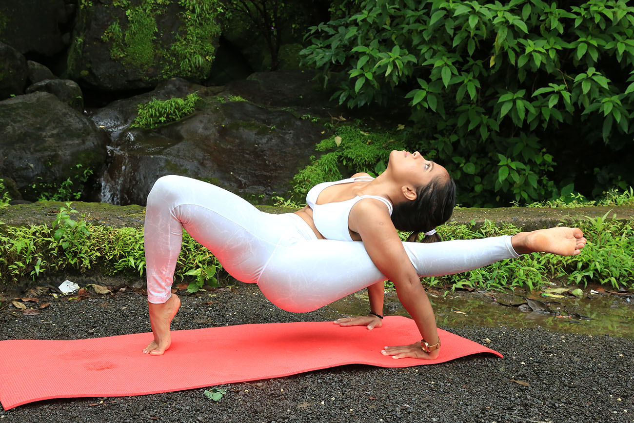 a girl performing the Shiva pose in Yoga