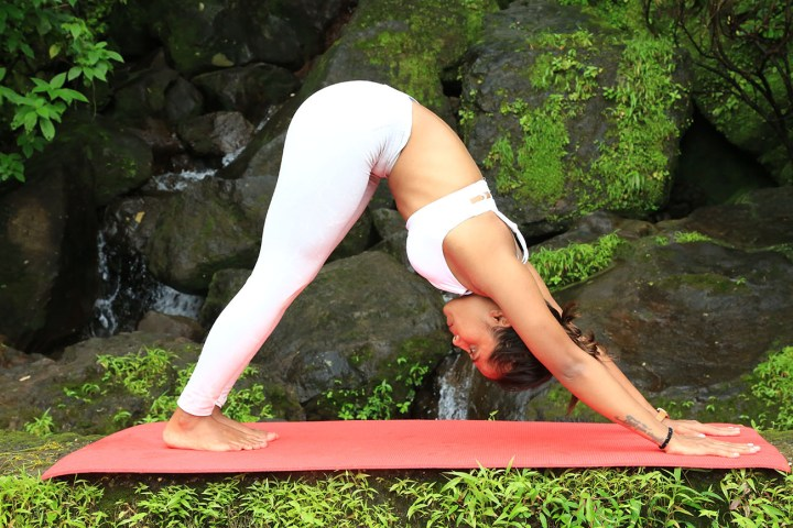 a girl performing the Downward dog pose in yoga as part of an ab routine