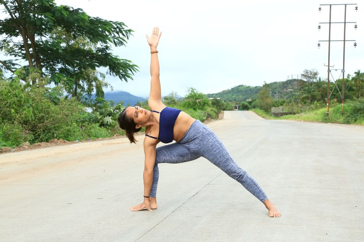a girl performing the triangle pose for a healthy spine