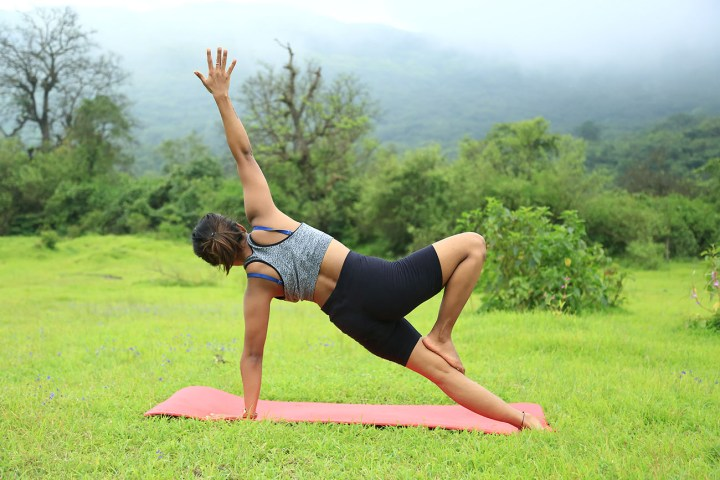 a girl performing the side plank pose in yoga