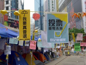 """Many tents are set up at the Causeway Bay Camp. The banners read """"I want real universal suffrage"""" on the left and Vote, Reclaim our future."""""""