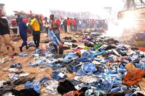 Stallkeepers salvage their belongings as rescuers and residents gather at the charred scene following a bomb blast at Terminus market in the central city of Jos on May 20, 2014