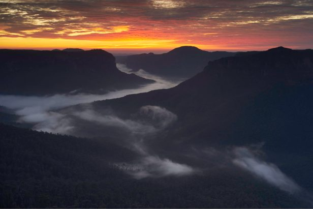 Political thriller novels and war novels.  Color photograph of misty hills with sunset behind them. Photographer, Matt Smith, https://www.flickr.com/photos/seven2photography/