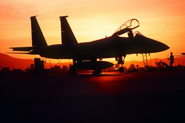 A colored photograph of F15 fighter silhouetted by rising sun  author  Aaron Yeoman