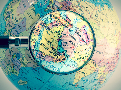 Globe of the world with the Middle East to the top and a magnifying glass over Iran and surrounding countries