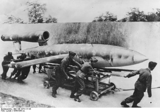 Black and white photograph of V1 missile being pulled along on a trolley by several air force men. Nazi Weapons of Mass Destruction.
