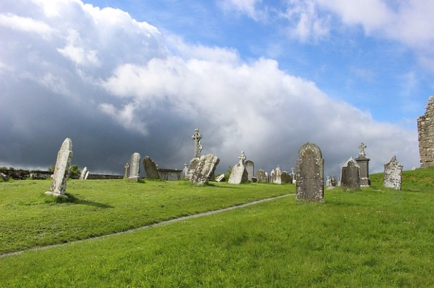 Colored photograph of a sprawling cemetery with scattered, dilapidated headstones and a brooding sky. Short fiction stories about the Holocaust.