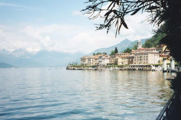 Colored photograph of Lake Como with buildings of town of Bellagio on lakeside. Snow-capped mountains in background. Authenticity.