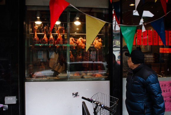 A passerby looks into the window of a restaurant in Chinatown. Photo by Brian Nunes.