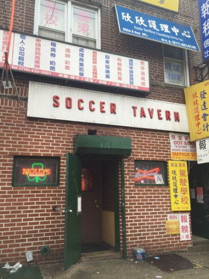 Just a red brick wall and a nondescript green door, flanked by two small windows with neon beer signs.