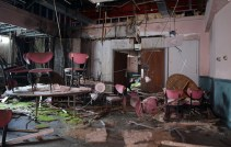 Chairs on tables and moss growing on floor in trashed dining area