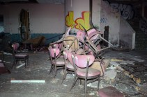 Pile of chairs in trashed dining area