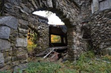 Looking through stone arch toward the collapsing porch beyond