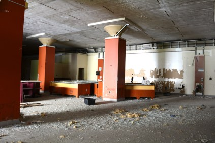 Scrapped cafeteria with red columns and counters within building complex
