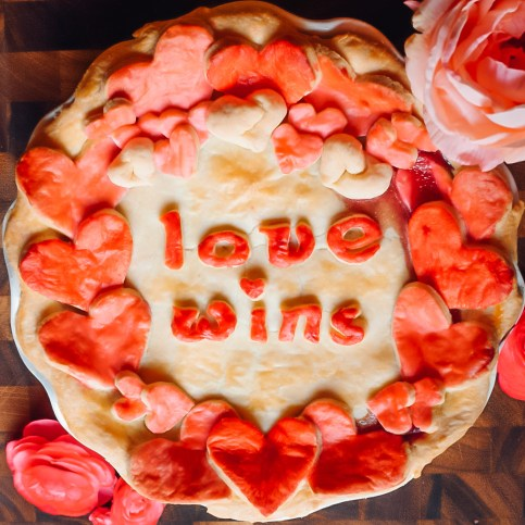 "Valentine's Day Pie covered in hearts that reads ""Love Wins"""