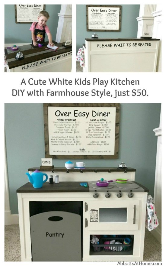A super cute white kids play kitchen DIY with Farmhouse Style and restaurant menu board. I built this for about $50 and it's so cute. Kids love the food pantry, diner menu, dinner bell, motion-activated microwave light, open and closed sign.