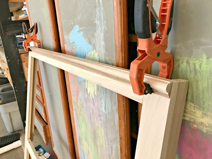 Clamps and glue hold the moulding onto the bed frame while I nail it in place.