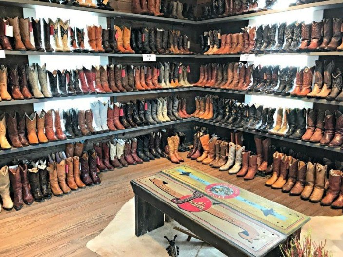 Room lined with shelves of cowboy boots. The Spring and Fall Round Top Texas Antiques and Flea Markets are great! BUT you can find Fun, Art & Furniture Shopping in Round Top, Texas year round, guys! Check out photos from the shops in town. #RoundTop #TexasTravel #AbbottsAtHome