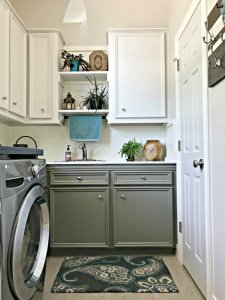 Creamy white cabinets and walls with grey lower cabinets, with plants, wood accents, and teal pops of color. This post is full of Before & After Makeover Photos, budget-friendly DIY ideas, and Laundry Room decor. #LaundryRoom #BeforeandAfter #AbbottsAtHome
