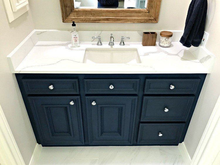 Marble Look Quartz Counters with a rectangle undermount sink and dark blue vanity. See all the details for this bathroom makeover here. #AbbottsAtHome #Quartz #Marble #Countertops #Bathroom #InteriorDesign