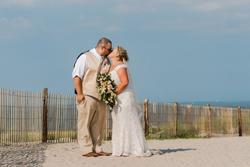 Wedding couple kissing on a beach in Lewes, Delaware