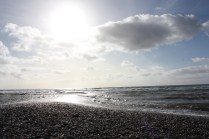 Waves crash onto the gravelled beach. The only splash of colour comes from the rays of the setting sun.