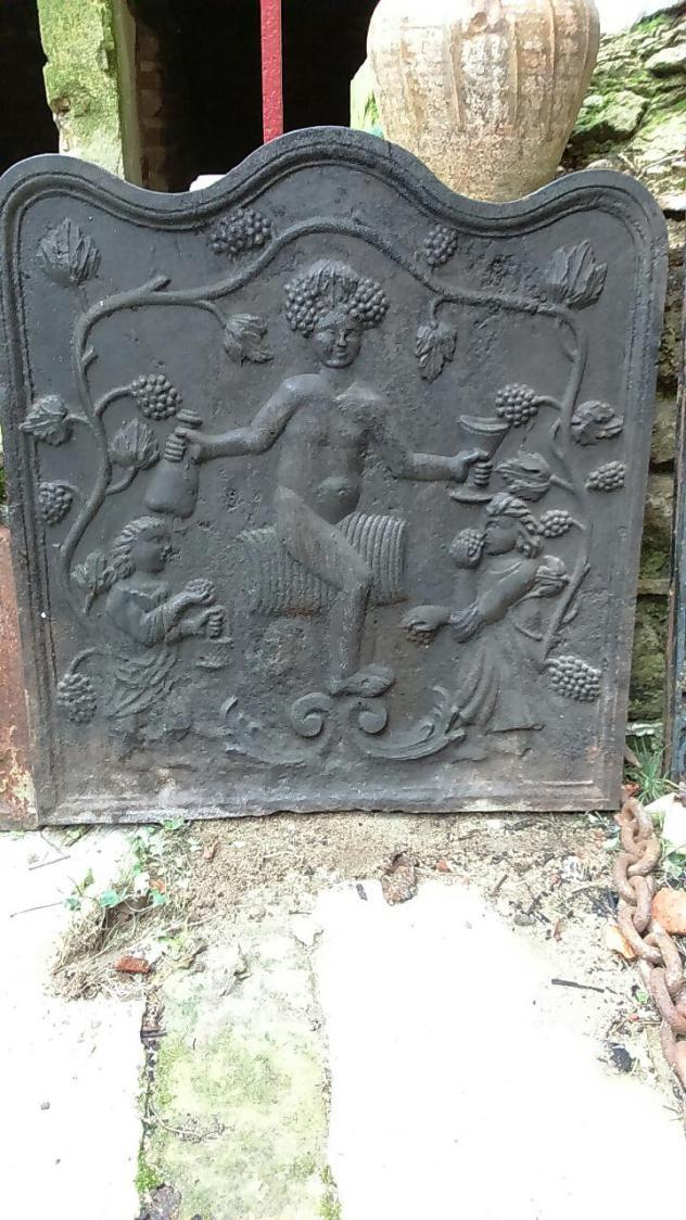 Plaque de cheminée en fonte  Bacchus assis sur un tonneau avec bouteille en main, entouré de vignes. (64x64 cm) € 250