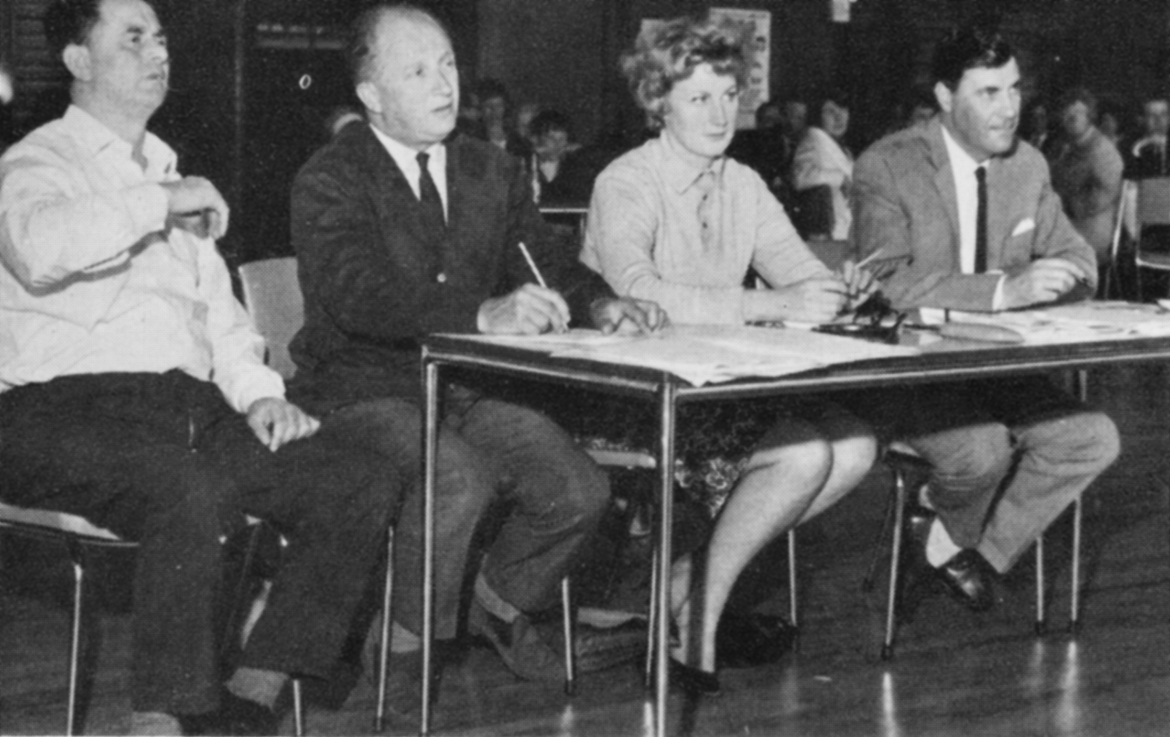 Three men and a woman behind a desk