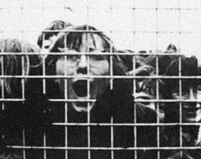 Girls scream behind a fence