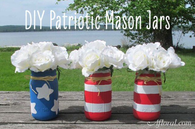 Red and white stripped and blue and white star mason jars filled with white flowers