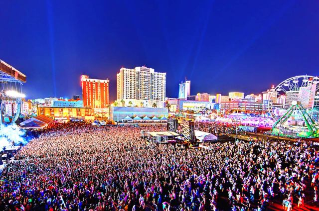 Drone photo of huge crowd at Las Vegas Life is Beautiful Musical Festival. Bright city lights and pigmented image.