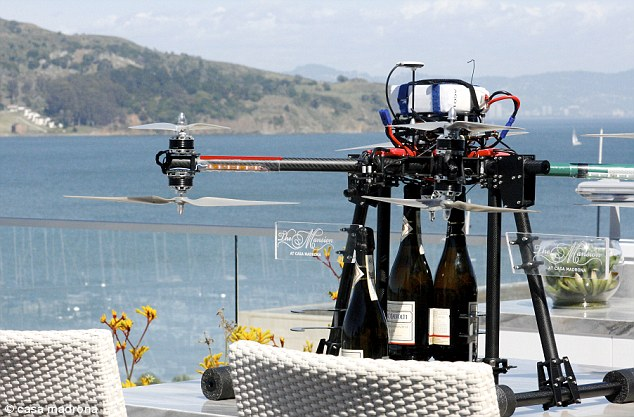 A drone holding champagne bottles on a table.
