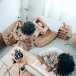 Canva - Faceless black kids drawing and playing on carpet at home