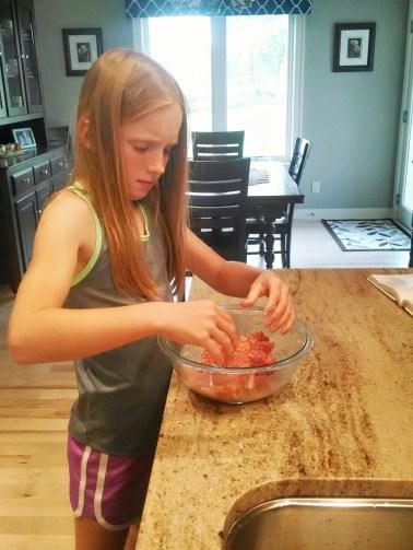 Grace mixing meatballs.