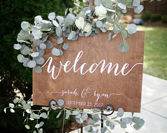 Wood wedding welcome sign with green garland