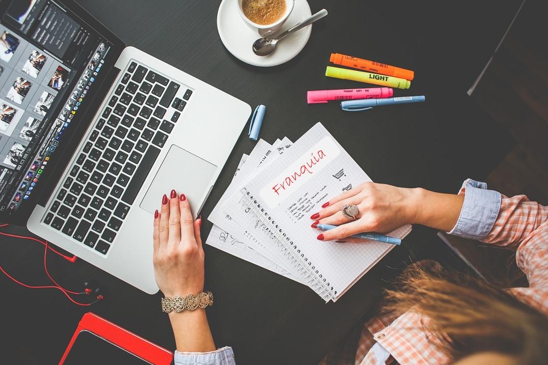 Imagem de uma mulher mexendo em um notebook e um caderno a sua frente com a idéia de abrir um negócio