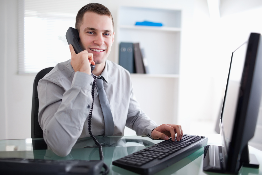 Foto de um rapaz digitando no computador e falando ao telefone, representando um empreendedor de primeira viagem