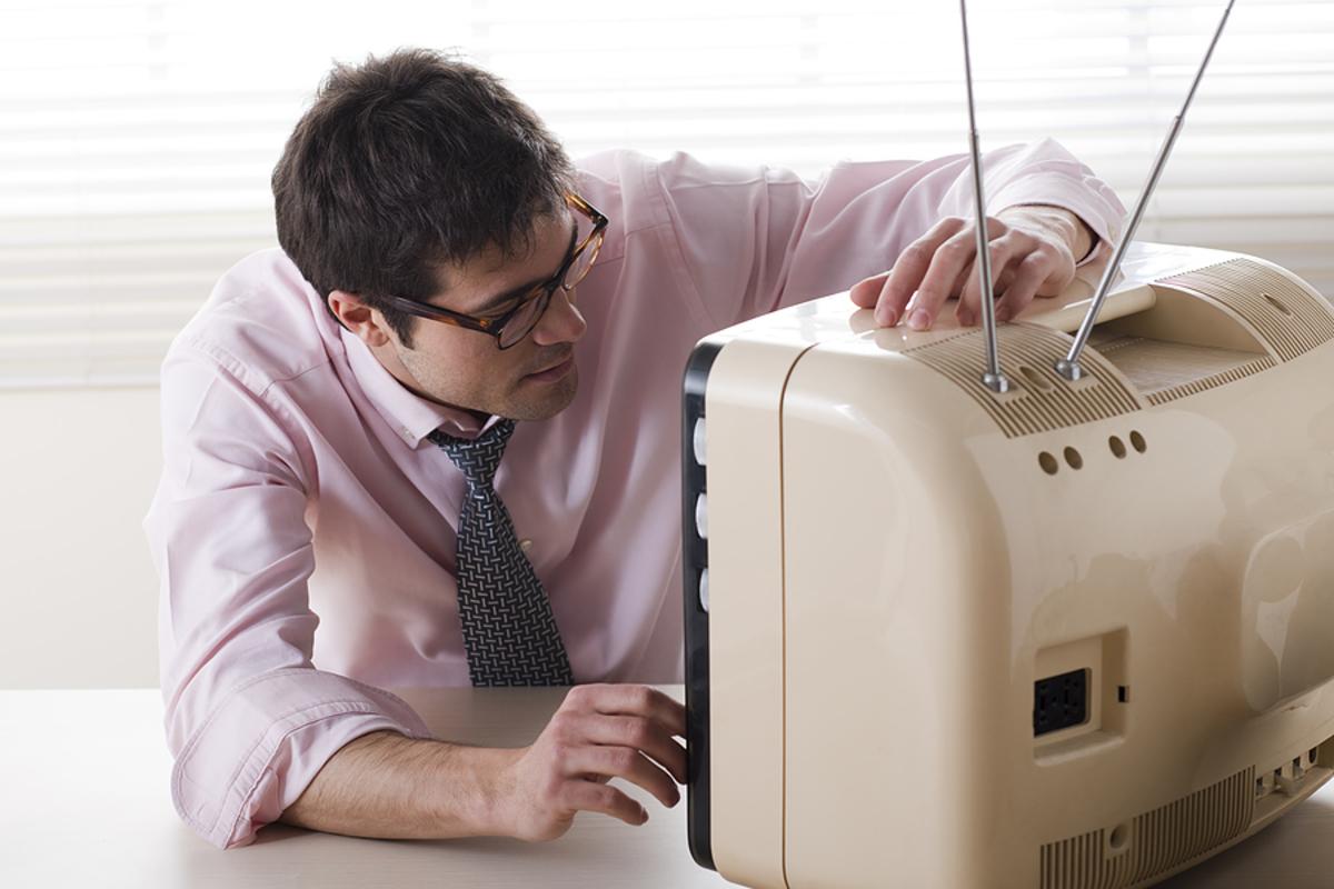 Foto de um homem assistindo uma televisão antiga, representando os filmes para empreendedores