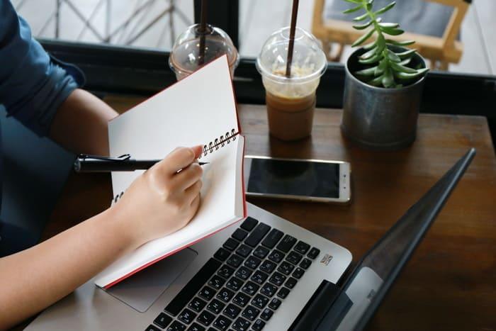 Pessoa com notebook e caderno, representando empreender em Cajamar - Abertura Simples