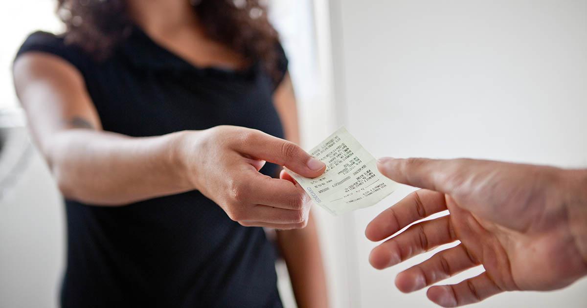 Foto de uma mulher entregando uma nota fiscal para outra pessoa, representando o processo para cancelar Nota Fiscal de Serviço Eletrônica