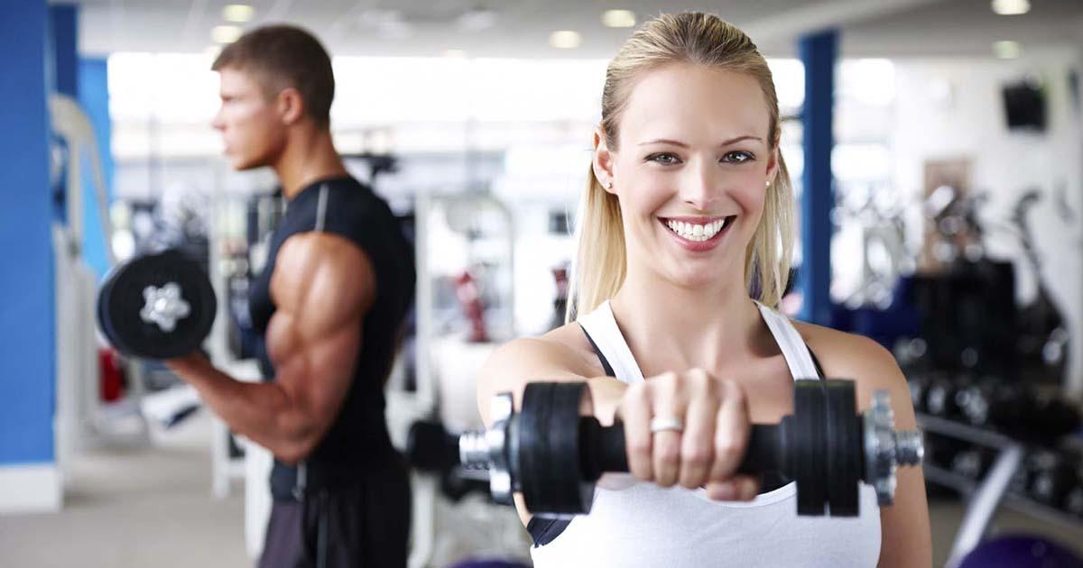 Foto de uma mulher levantando peso na academia, representando as franquias fitness