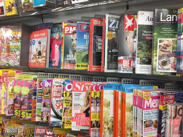 Foto de algumas revistas em uma prateleira, representando como abrir uma banca de revista