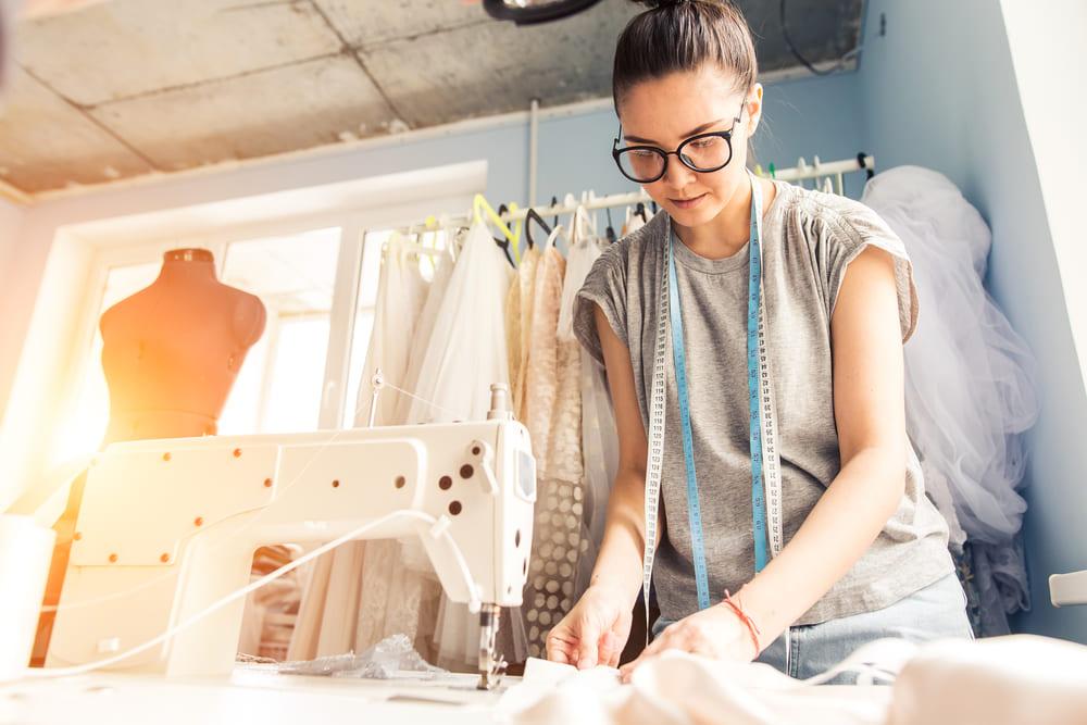 Foto de uma mulher fazendo costura, representando como abrir um atelier de costura